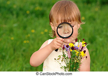 Child looking at flowers through magnifying glass - Cute...