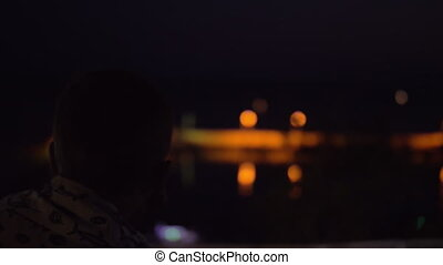 Child looking at night sea from the house balcony - Boy at...