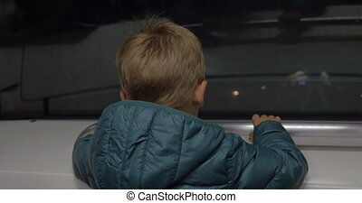 Child looking at railway from moving subway train
