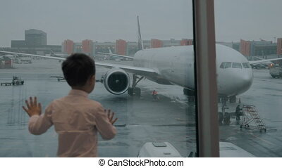 Child looking at the airplane through the window