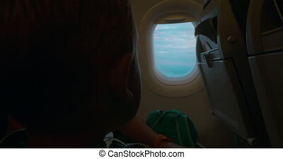 Child looking out the illuminator in plane