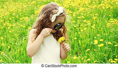 Child looking through a magnifying glass on the grass in summer day