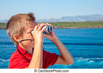 Boy sailing on cruise ship looking through binoculars