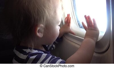 Child looking through porthole in an airplane - Baby boy...