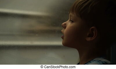 Child looking through the window of moving train