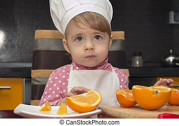child looking up in surprise. portrait little cute girl in chef suit with orange. 2 year old.