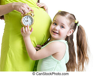 child looks at alarm clock and pregnant woman belly