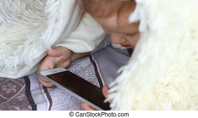 Child Looks cartoons and plays downloaded application on a smart phone close-up. A little cute funny girl lies in bed under the blanket and looks at the white phone screen