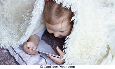 Child Looks cartoons and plays downloaded application on a smart phone close-up. A little cute funny girl lies in bed under the blanket, smilling and looks at the white phone screen.