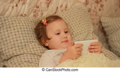 Child Looks cartoons and plays downloaded application on a smart phone close-up. A girl lies in bed and looks at the white phone screen.