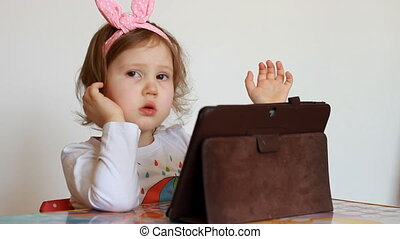 Child looks on the tablet screen and plays downloaded...