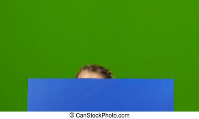 Child looks out from behind a blue board and shows a thumbs...