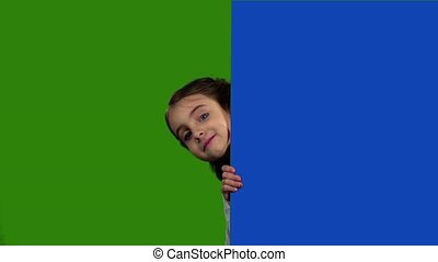 Child looks out from behind an empty board. Green screen....