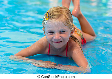child lying in the shallow water