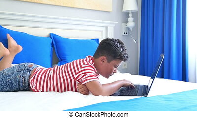 Child lying on a bed and using laptop computer