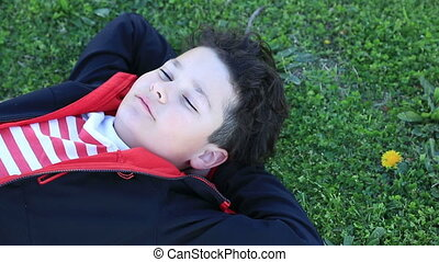 Child lying on green grass and relaxing