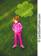 Child lying on the green grass in park under lighting cloud.
