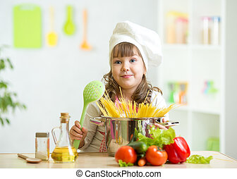 Child makes healthy vegetables meal in the kitchen