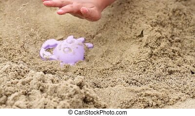 child makes of sand - Person creating a sand shape with a...