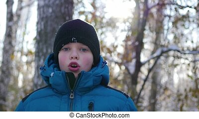 child makes steam of mouth on a cold sunny day
