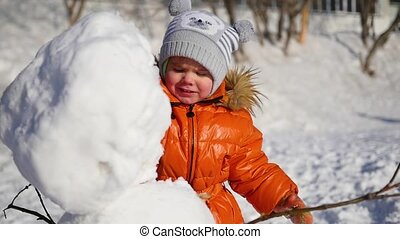 child making a snowman in the Playground - child sculpts a...