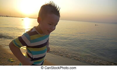 Child making angry face on the beach at sunset