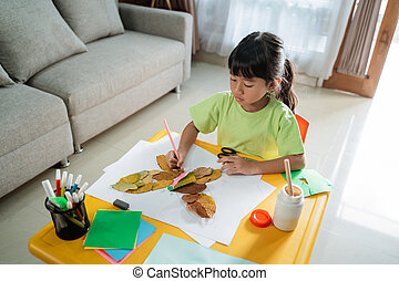 child making art from dry leaves