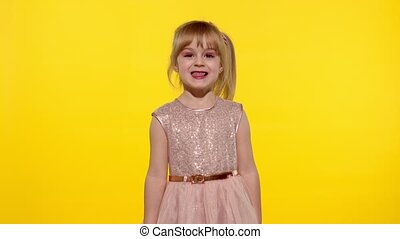 Child making faces, fooling around, showing tongue. Little blonde teen kid girl 5-6 years old posing
