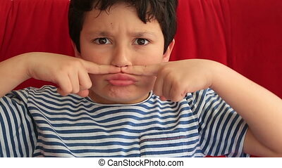 Child making funny silly faces - Happy school boy making...