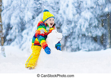 Child making snowman. Kids play in snow in winter