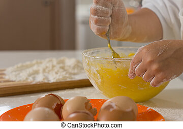 Child mixing ingredients in a mixing bowl