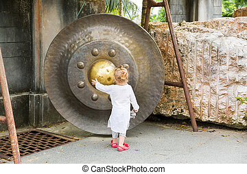 Child near Thai gong in Phuket. Tradition asian bell in...