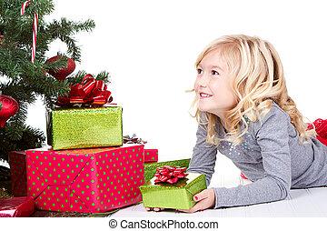 Child next to a Christmas tree