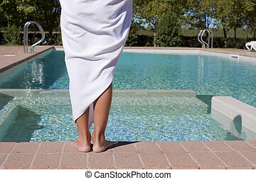 A person wrapped up in a towel standing with back to camera looking at an empty swimming pool