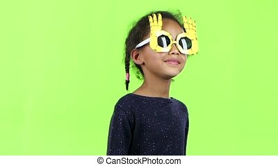 Child of an african american girl dancing in funny glasses. Green screen. Slow motion