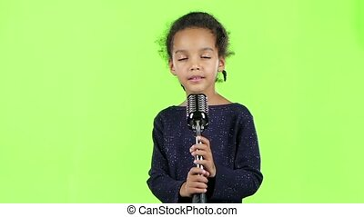 Child of an african american girl singing in a retro microphone. Green screen. Slow motion