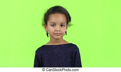 Child of an african american girl singing in a retro microphone. White background. Slow motion