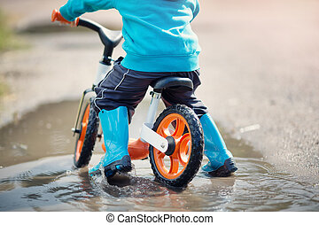 child on a bicycle. Boy in wellies in puddle on rainy weather