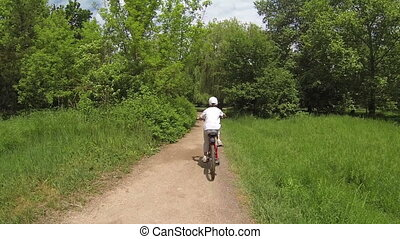 Child on a bike. View from behind