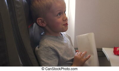 Child on a plane, he is vomits and he is holding a special package for vomiting.