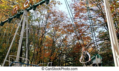 Child on a swing in the autumn park