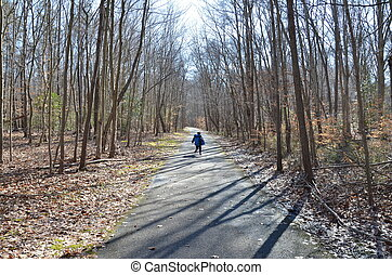 child on asphalt trail or path in forest or woods