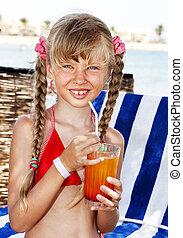 Child on beach drinking cocktail.