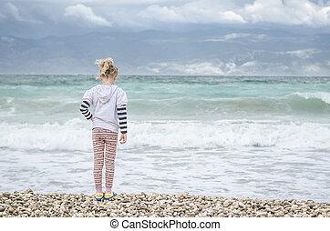 child on beach looking to wild sea