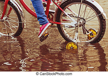 Child on bike rides through a puddle in autumn day.