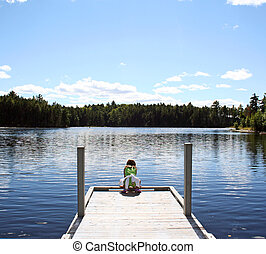 Child on dock at lake