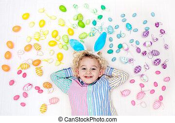 Child on Easter egg hunt. Pastel rainbow eggs. - Funny...