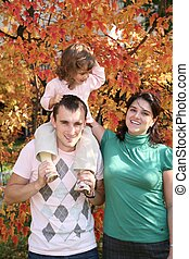 child on father`s shoulders with mother in the park