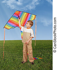 child on grass with kite, collage