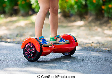 Child on hover board. Kids ride scooter. - Child on hover...